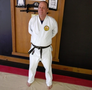 Sensei Steve Jansen standing in white karate uniform and black belt.
